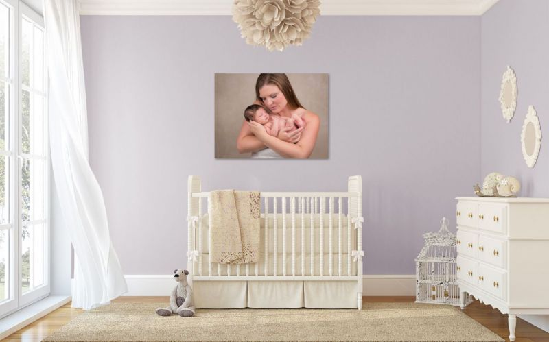 Beautiful photograph of newborn baby and mother hanging on the wall in the nursery.
